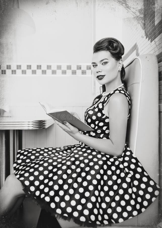 Retro- Weinleseporträt der netten jungen Frau, die im Café mit Buch sitzt Pin herauf das Artporträt der jungen Frau im Kleid, sch lizenzfreies stockfoto