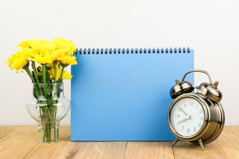 Retro wekker en bloemen stock foto
