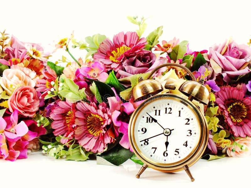 Retro wekker met bloemen op witte achtergrond stock foto