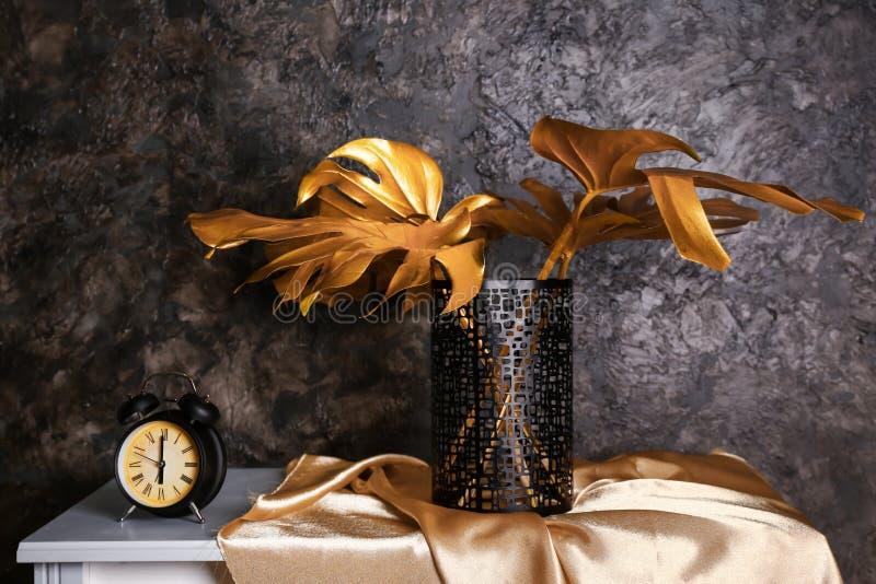 Retro wekker met gouden tropische bladeren op lijst dichtbij donkere muur stock foto