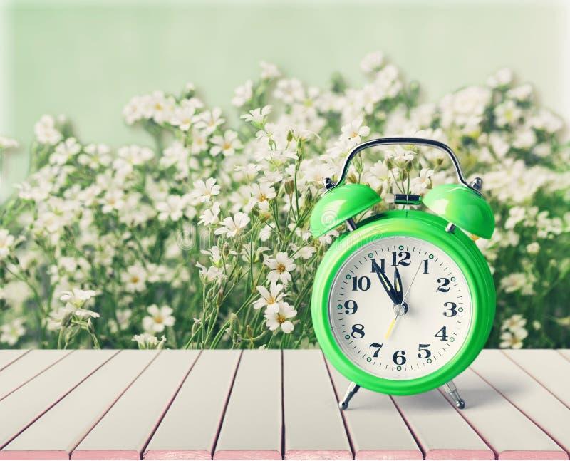 Retro wekker op bloemenachtergrond stock afbeelding