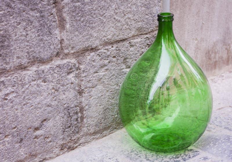 Retro wielka zielonego szkła wina butelka na chodniczku fotografia stock