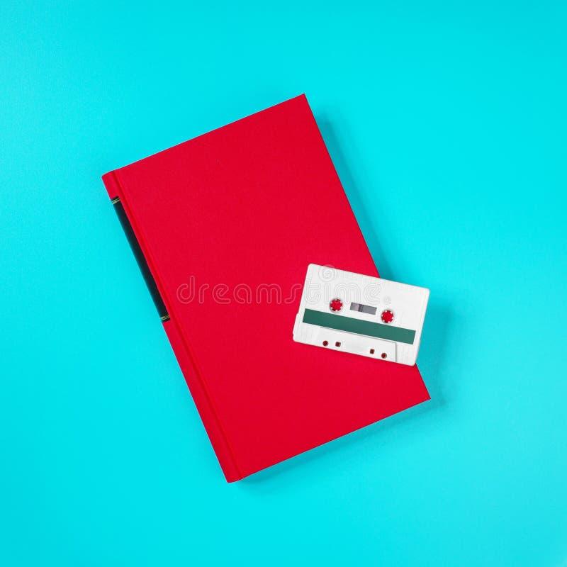 Retro witte plastic audiocassette en rood boek die op de groene metaallijst leggen royalty-vrije stock foto