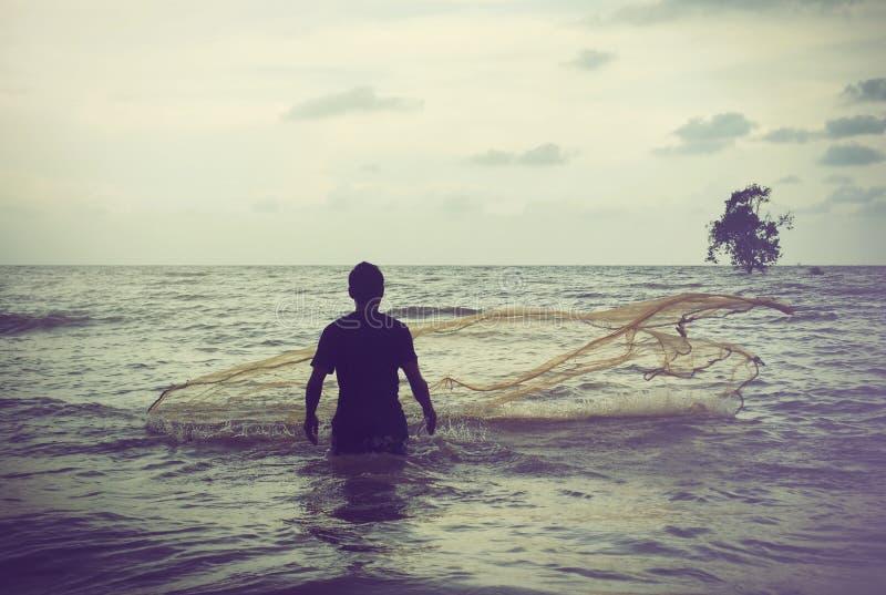 Retro wizerunku pojęcia rybak rzuca jego sieć rybacką podczas zmierzchu zdjęcia royalty free
