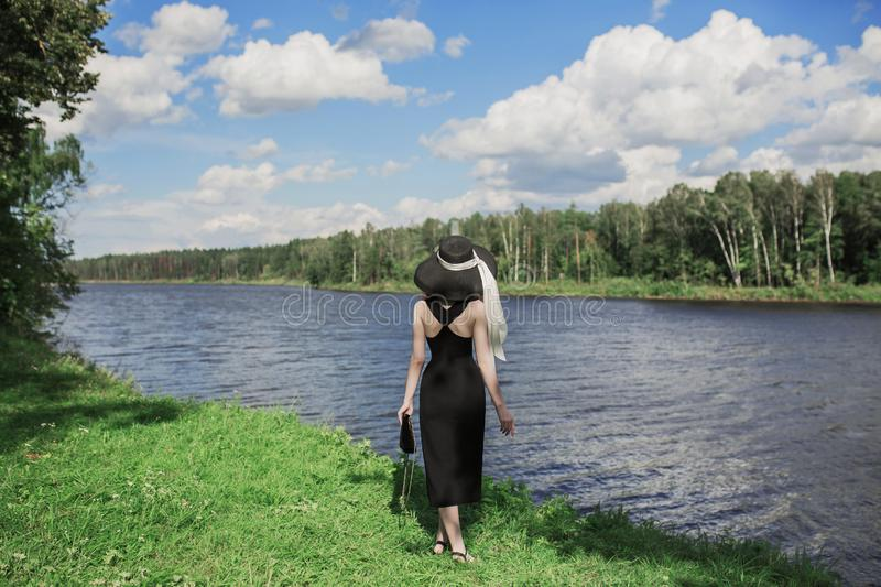 Retro woman in black dress on picturesque summer background. Vintage girl on background of forest with green leaves. Blue river. Flowing across the plain stock photos