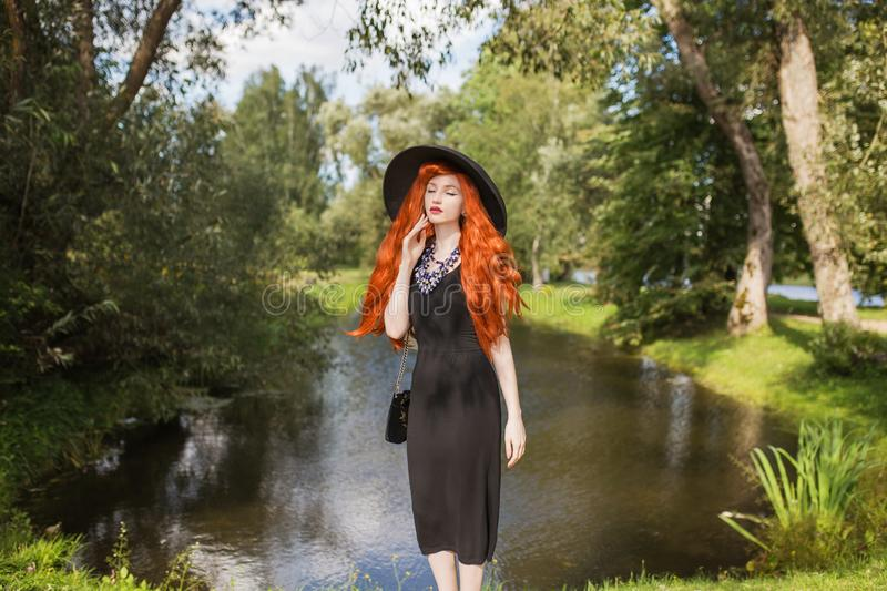 Retro woman in black dress on summer background. Slim redhead model in hat. Vintage girl on background of forest with green leaves. Beautiful sunny landscape royalty free stock photo