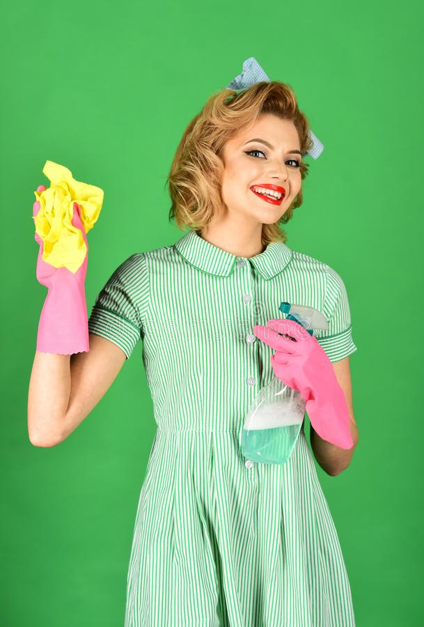 Retro woman cleaner on green background. Housekeeper in uniform with clean spray, duster. Cleanup, cleaning services, wife, gender. Cleaning, retro style royalty free stock images