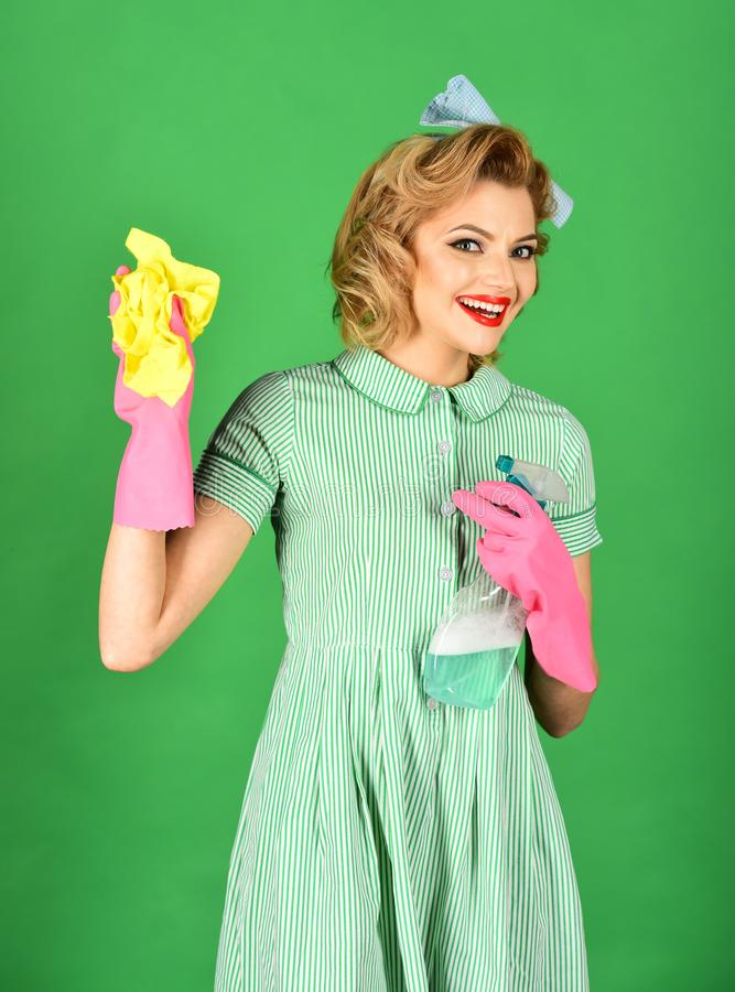 Retro woman cleaner on green background. Housekeeper in uniform with clean spray, duster. Pinup woman hold soup bottle, duster. Cleaning, retro style, purity royalty free stock images