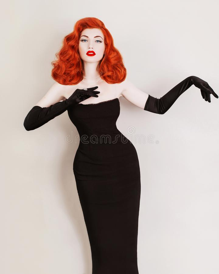 Retro woman with curly hair in black dress and long gloves on gray background. Redhead girl with red lips is dressed in retro. Style. Slim retro model in long royalty free stock image