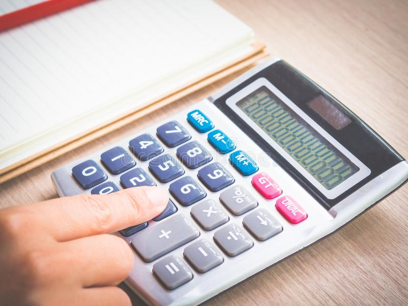 Retro woman hand working with calculator, red pencil and note book on working table. stock photography
