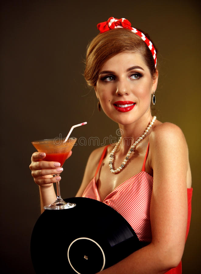 Retro woman with music vinyl record. Pin up girl drink martini cocktail. Pin-up retro female style. Girl pin-up style wearing red dress royalty free stock photo