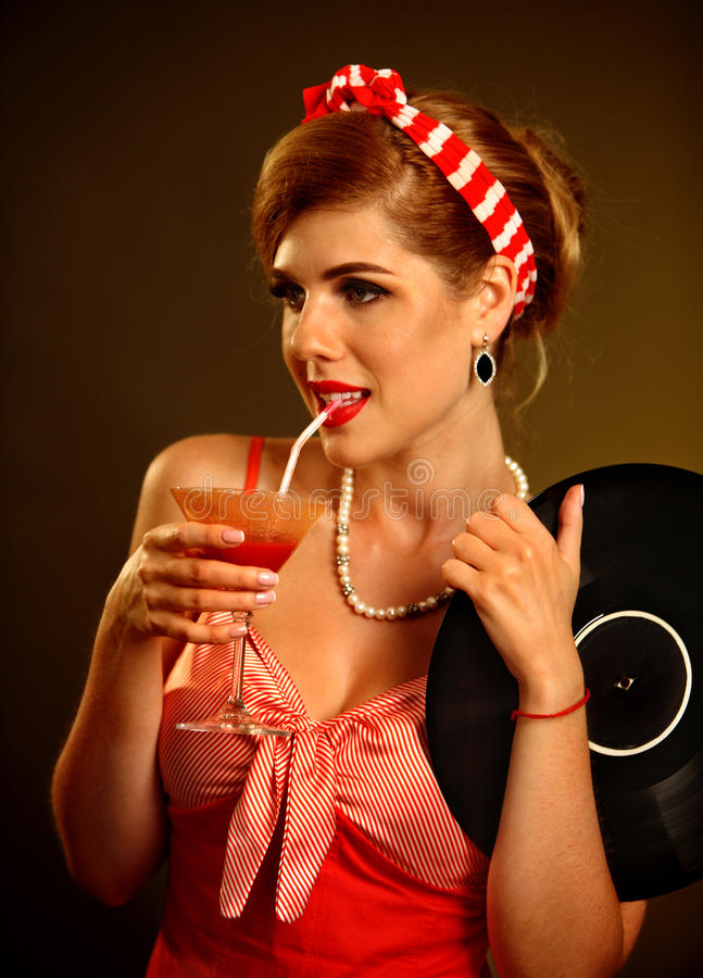 Retro woman with music vinyl record. Pin up girl drink martini cocktail. Girl pin-up retro style wearing red dress on dark background royalty free stock photography