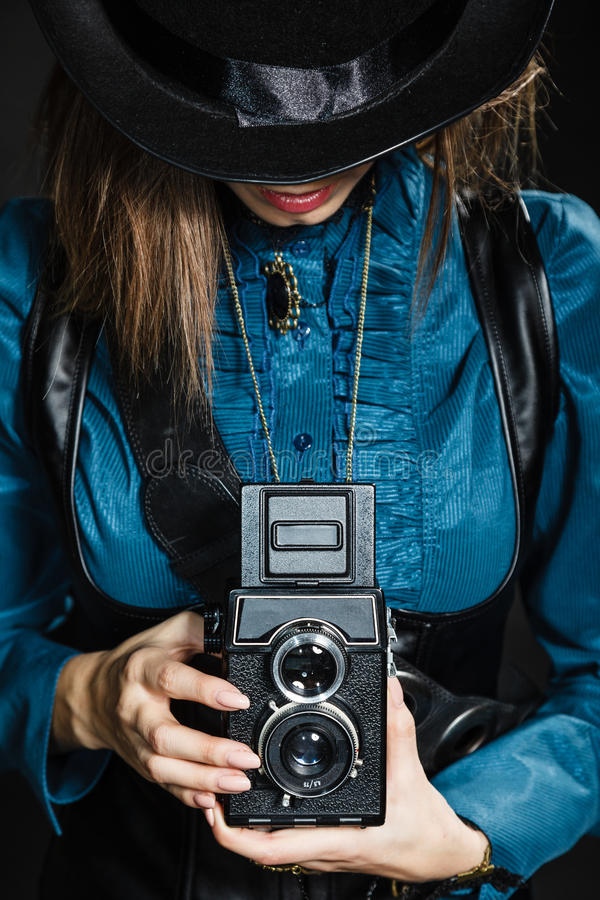 Retro woman with old camera. Steampunk. stock photography