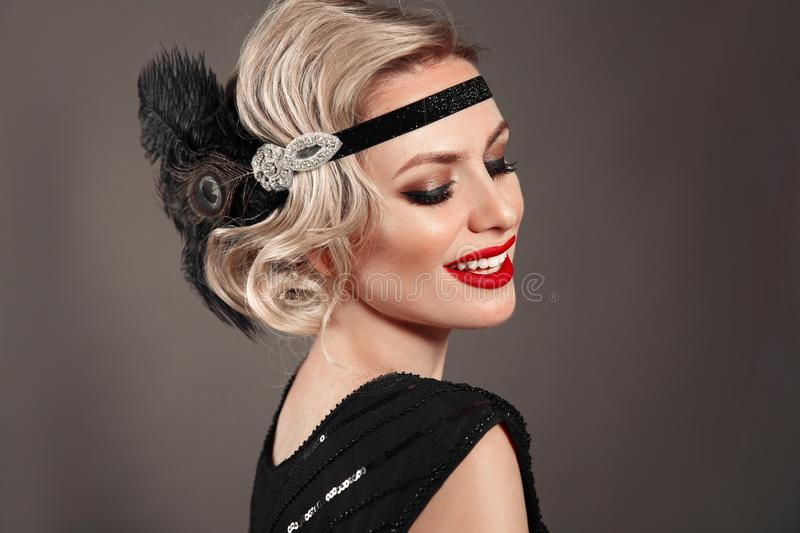 Retro woman portrait. Blonde wavy hairstyle. Hollywood red lips makeup. Curly hair style. Beautiful elegant female wears in. Vintage dress isolated on dark stock photos