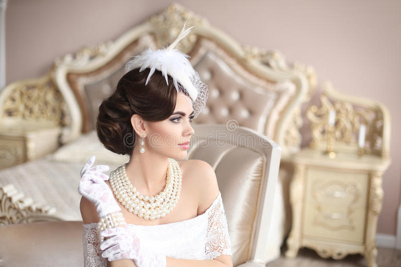 Retro woman portrait. Elegant brunette lady in hat with hairstyle, pearls jewelry set. Pretty female posing on modern armchair in. Luxury bedroom interior royalty free stock photos