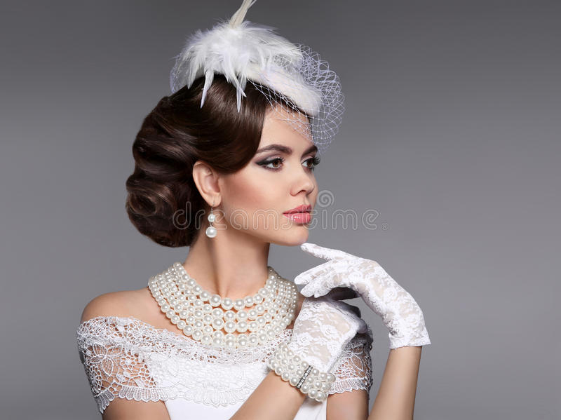 Retro woman portrait. Elegant lady with hairstyle, pearls jewelry set wears in hat and lace gloves posing isolated on studio gray royalty free stock image