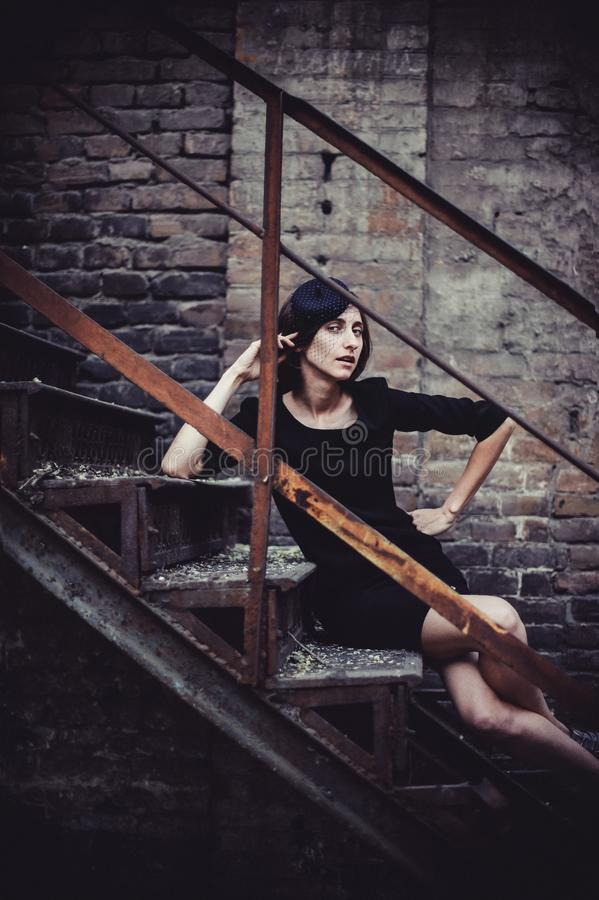 Retro Woman Portrait. Vintage Style Girl Wearing Old fashioned Hat. Romantic lady sitting on vintage forged staircase. Selective f royalty free stock photos