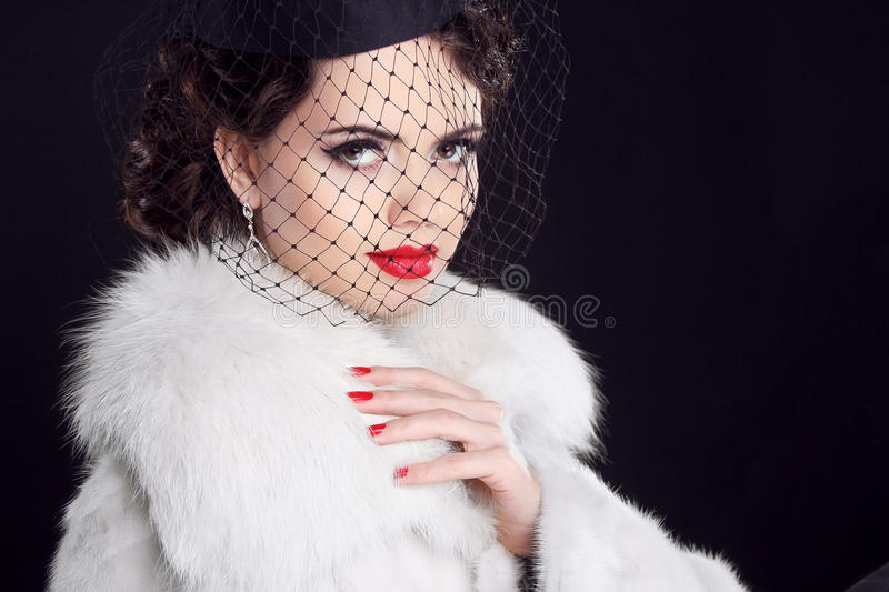 Retro woman posing in luxury fur coat. Fashion model girl portrait Isolated on black background. stock images