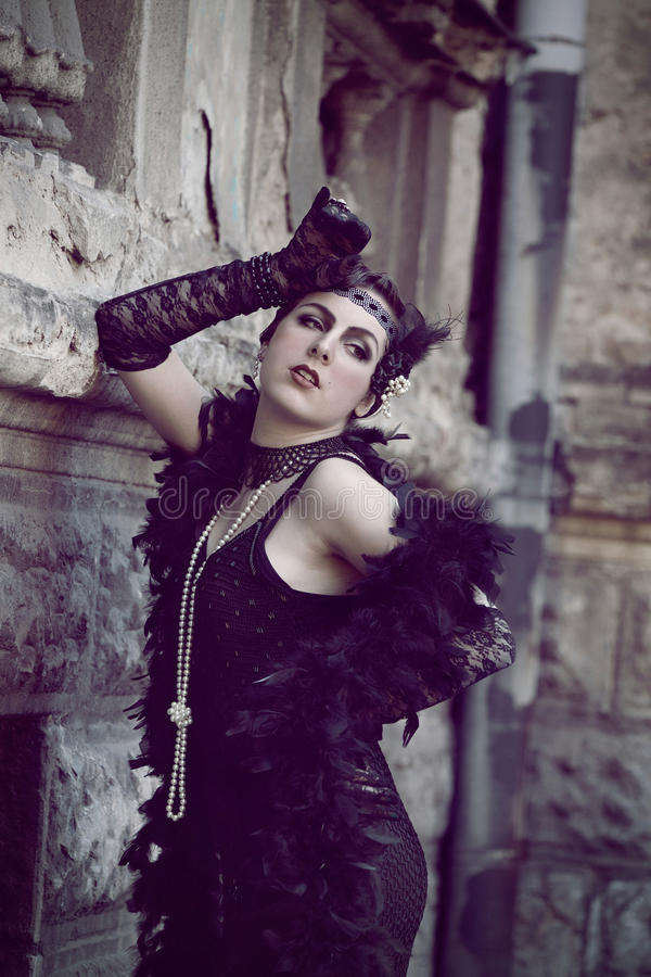 Retro Woman 1920s - 1930s. The Beautiful Retro woman in Black Lace and Accessories in Style 1920s - 1930s Standing near Obsolete Wall stock photos