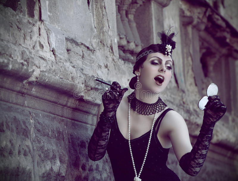 Retro Woman 1920s - 1930s. The Beautiful Retro woman in Black Lace and Accessories in Style 1920s - 1930s Standing near Obsolete Wall with Cigarette Holder and royalty free stock images