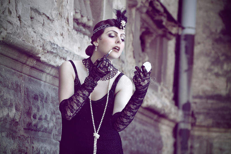 Retro Woman 1920s - 1930s. The Beautiful Retro woman in Black Lace and Accessories in Style 1920s - 1930s Tinting the Lips near Obsolete Wall with Small Round royalty free stock photos