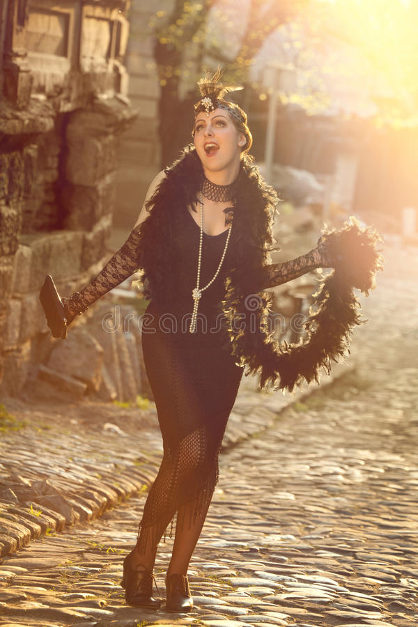 Retro Woman 1920s - 1930s in Rays of Setting Sun. Full Length Portrait of The Beautiful Retro woman in Black Lace, Accessories and Feather Boa in Style 1920s royalty free stock photo