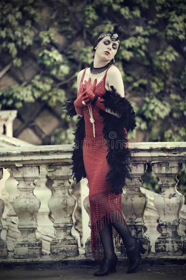 Retro Woman 1920s - 1930s in Red Dress. Full Length Portrait of The Beautiful Retro woman in Red Dress and Accessories in Style 1920s - 1930s Standing at the Old royalty free stock photo