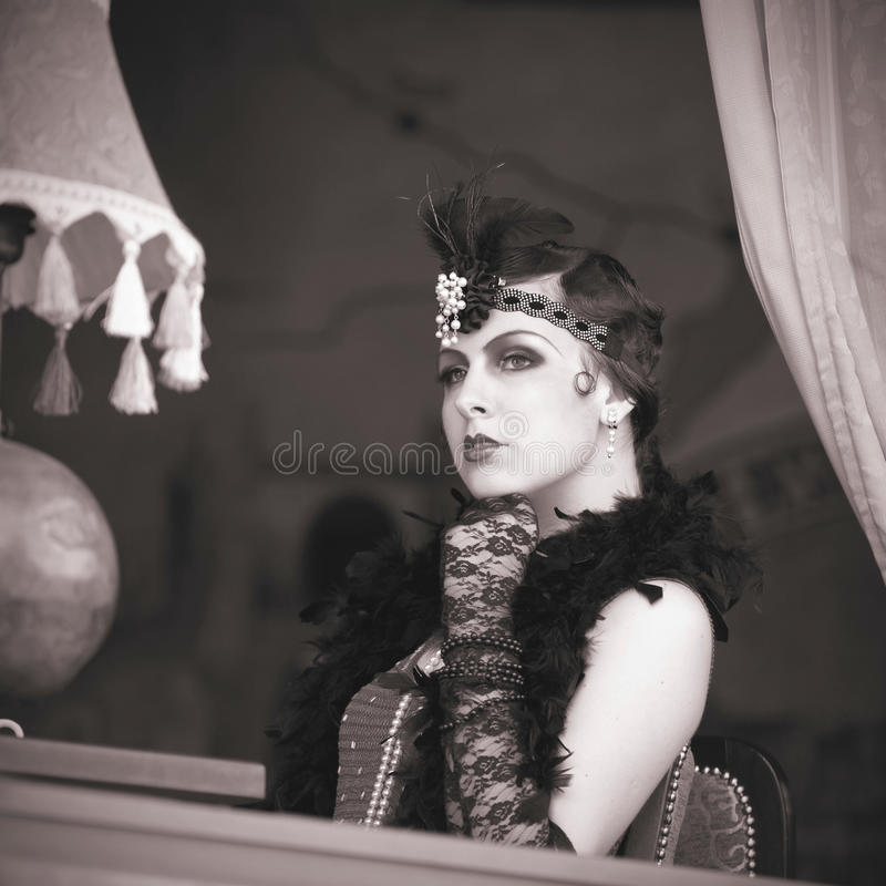 Retro Woman 1920s - 1930s Sitting in the Cafe. Black and White Portrait of The Beautiful Retro woman Sitting in the Cafe in Black Lace and Accessories in Style royalty free stock image