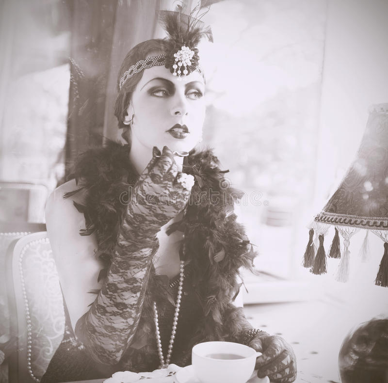 Retro Woman 1920s - 1930s Sitting in the Cafe. Sepia Portrait of The Beautiful Retro woman Drinking Tea in the Cafe in Red Dress and Accessories in Style 1920s stock photography