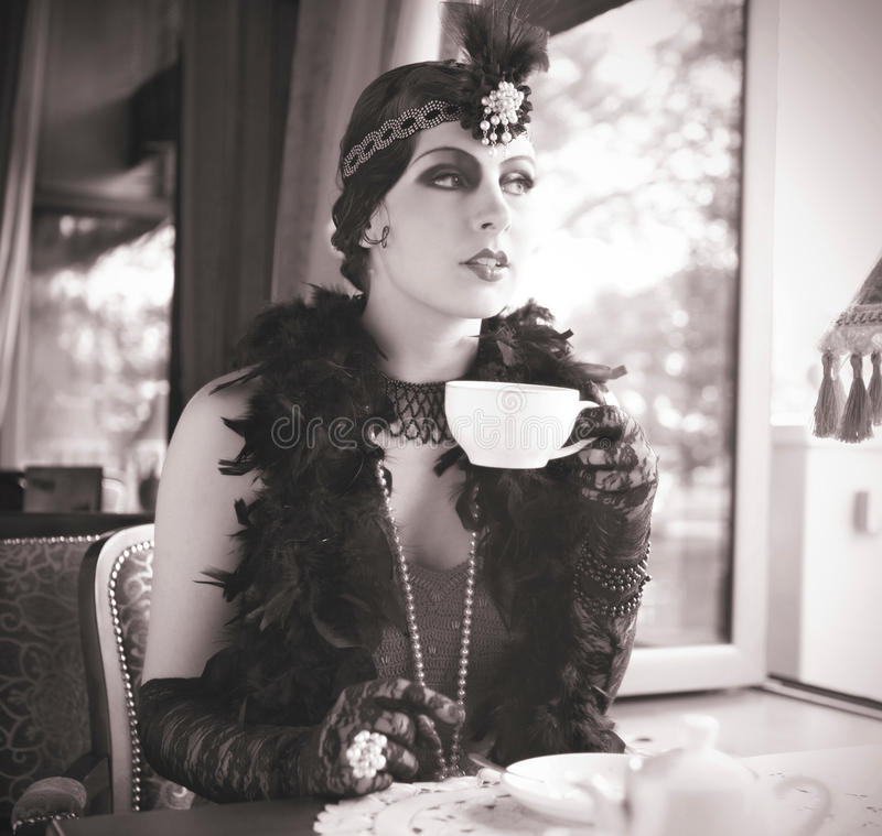 Retro Woman 1920s - 1930s Sitting with Cup of Tea. Black and White Portrait of The Beautiful Retro woman Drinking Tea in the Cafe in Black Lace and Accessories royalty free stock photography