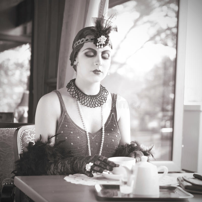 Retro Woman 1920s - 1930s Sitting with Cup of Tea. Black and White Portrait of The Beautiful Retro Woman Pouring Tea from a Teapot in the Cafe in Black Lace and royalty free stock photo