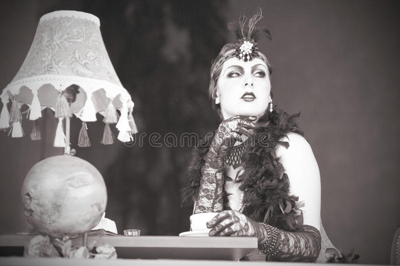 Retro Woman 1920s - 1930s Sitting with in a Restaurant Holding a. Retro Charleston Woman Fashion of 1920 - 1930 Sitting with in a Restaurant Holding a Cup of Tea stock images