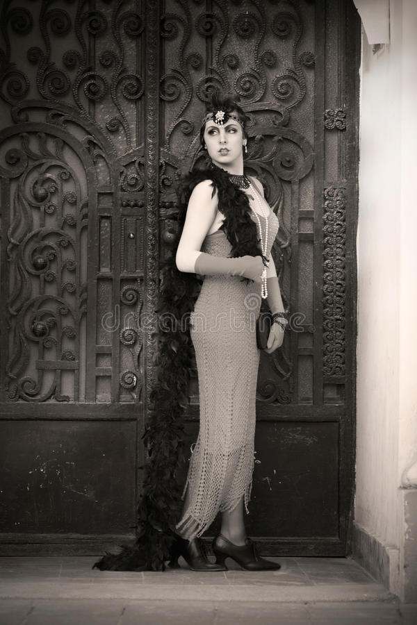 Retro Woman 1920s - 1930s Standing in the Gate. Full Length Portrait of The Beautiful Retro woman in Black Lace and Accessories in Style 1920s - 1930s Standing stock photos