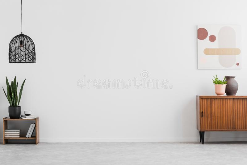 Retro, wooden cabinet and a painting in an empty living room interior with white walls and copy space place for a sofa. Real photo.  stock images
