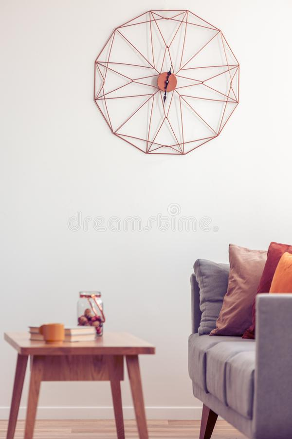 Retro wooden coffee table in front of grey couch in classy living room interior stock image
