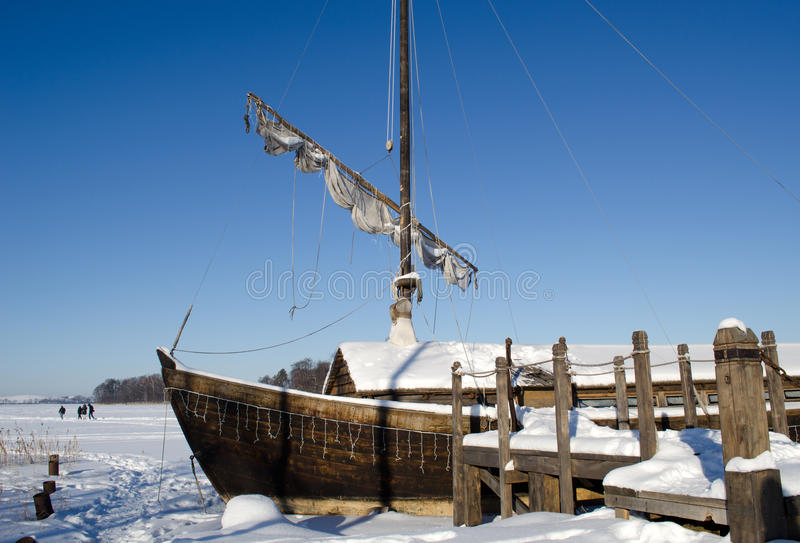 Retro wooden ship frozen lake ice sail people walk. Retro wooden ship frozen in lake ice near pier and sail on background of blue sky. people recreate in nature stock images