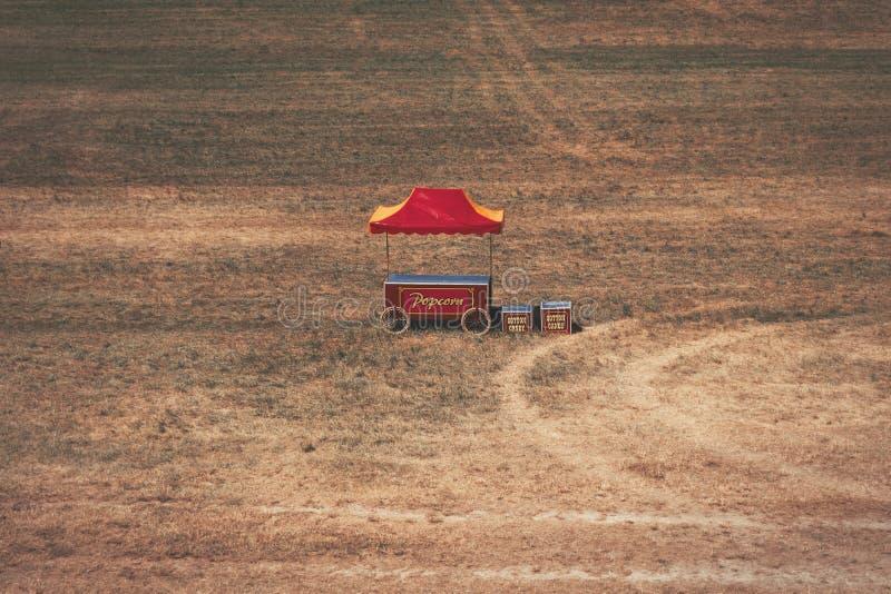 Retro wystrzał kukurudzy stojak, czerwień i kolor żółty stoi po środku nigdzie w dużym polu, zdjęcia stock