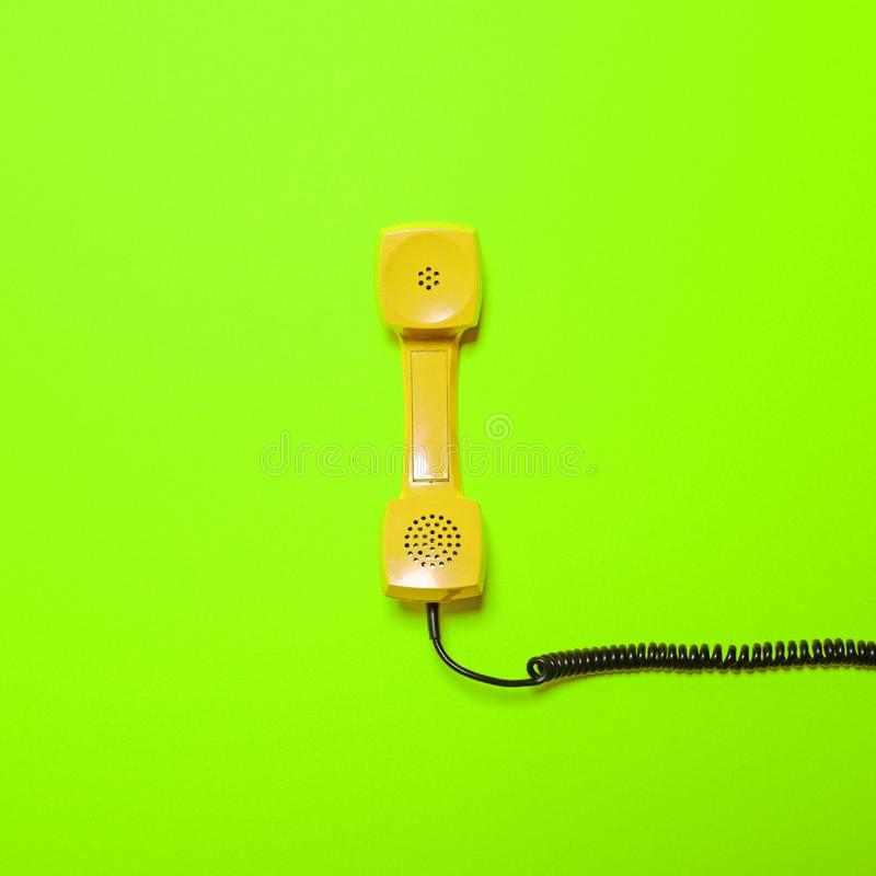 Retro yellow telephone tube on fluorescent green background - Minimal design royalty free stock image