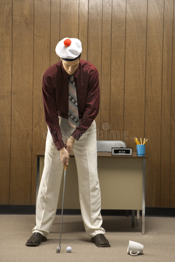 Retro zakenman speelgolf in bureau. stock fotografie
