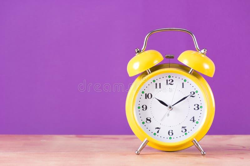 Retro zegar z dzwonem na drewnianym biurka i purpur tle obrazy stock