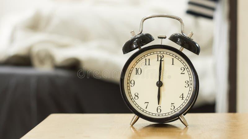 Retro zwarte wekker toont 6 uur in de ochtend stock afbeelding