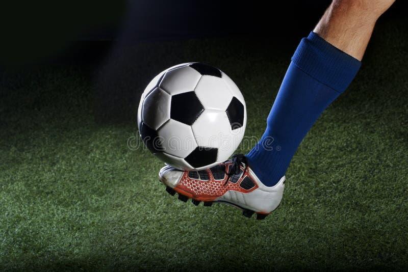 Retroceso del balón de fútbol con el pie en un campo de hierba en la noche imagenes de archivo