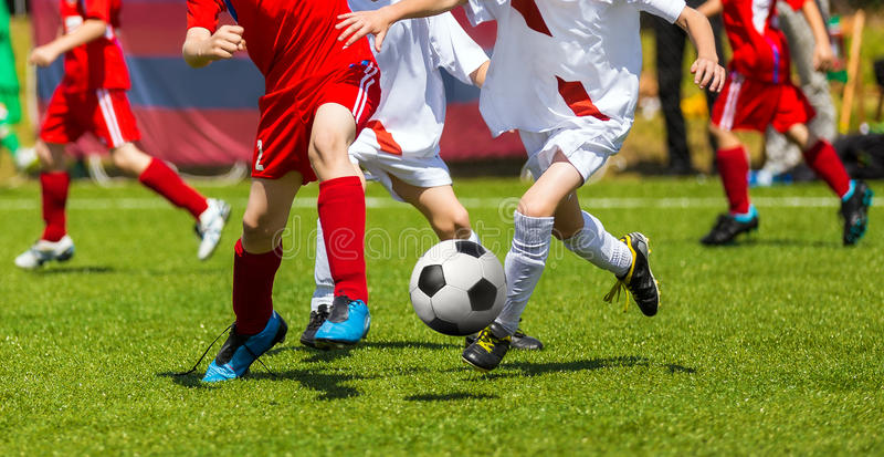 Retroceso del fútbol del fútbol Duelo de los jugadores de fútbol Niños que juegan al partido de fútbol en campo de deportes Parti foto de archivo libre de regalías