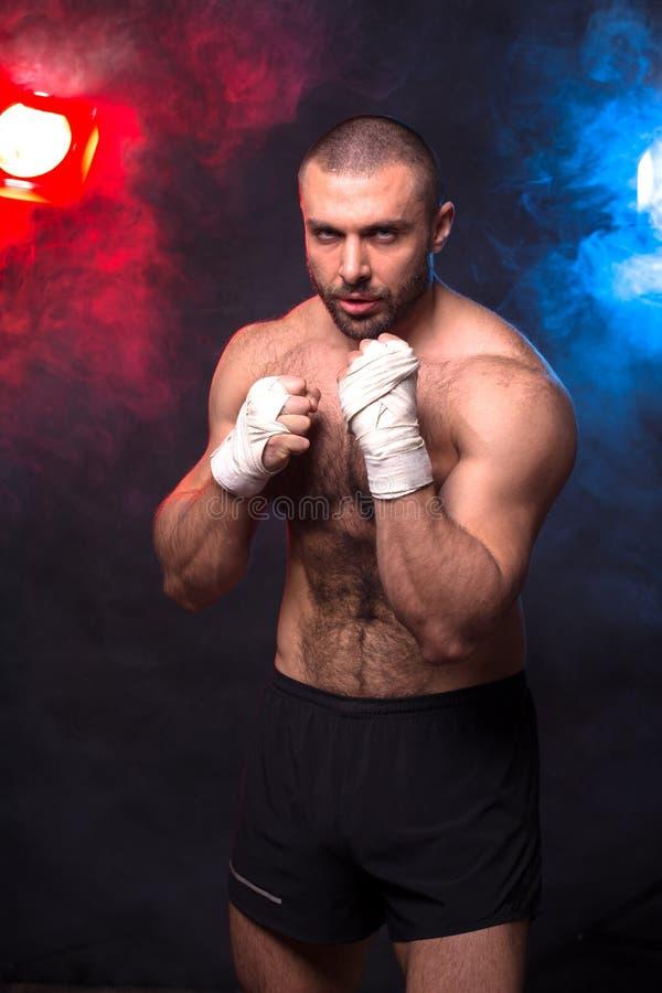 Retrocesos de encajonamiento musculares jovenes del entrenamiento del combatiente Kickboxer que hace un ejercicio que lucha imagen de archivo
