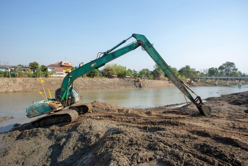 Retroexcavadoras que cavan la arena con las palas Del r?o foto de archivo libre de regalías