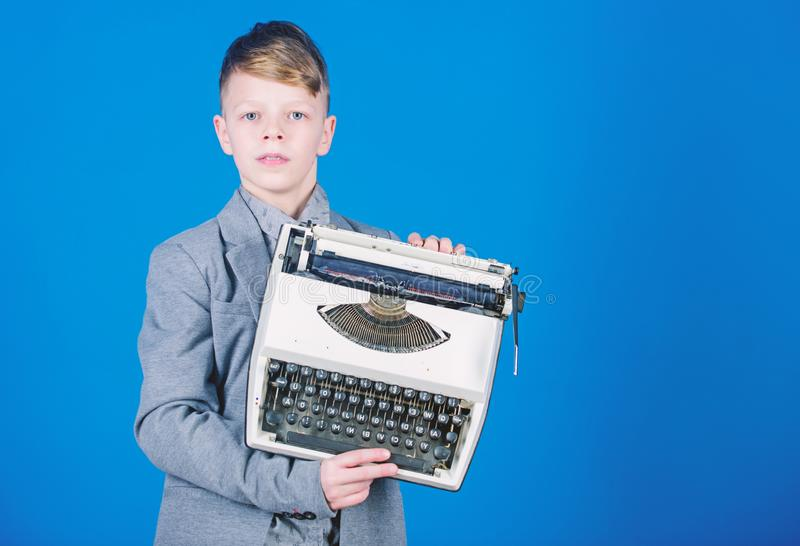 Retrospective study. Boy hold retro typewriter on blue background. What to do with this thing. Out of date. I need. Modern gadget instead this retro. Outdated stock photo
