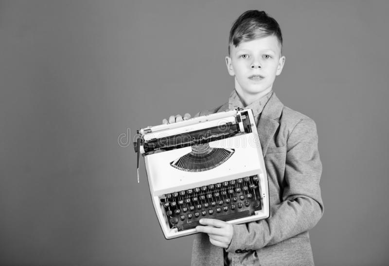 Retrospective study. Boy hold retro typewriter on blue background. What to do with this thing. Out of date. I need. Modern gadget instead this retro. Outdated royalty free stock photos