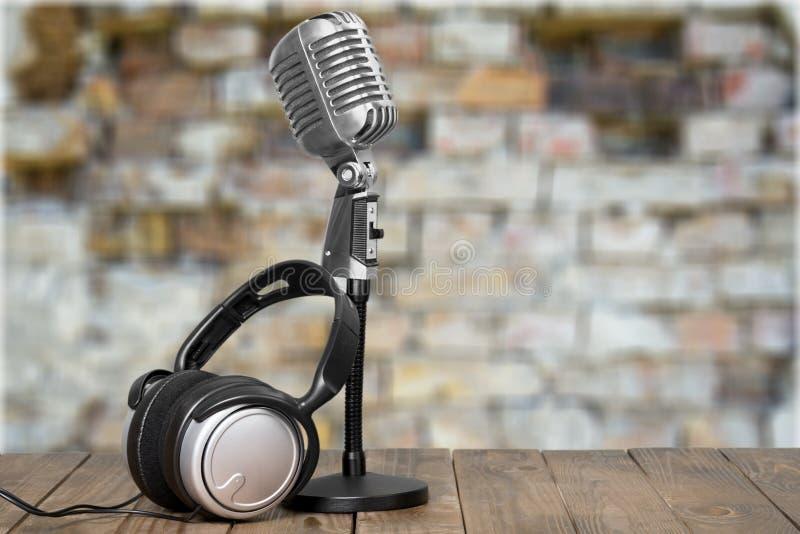 Retrostilmikrofon und -kopfhörer auf hölzernem stockbilder