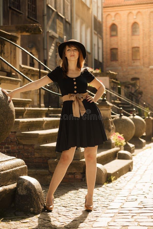 Retrostilmodefrau in der alten Stadt lizenzfreie stockfotografie