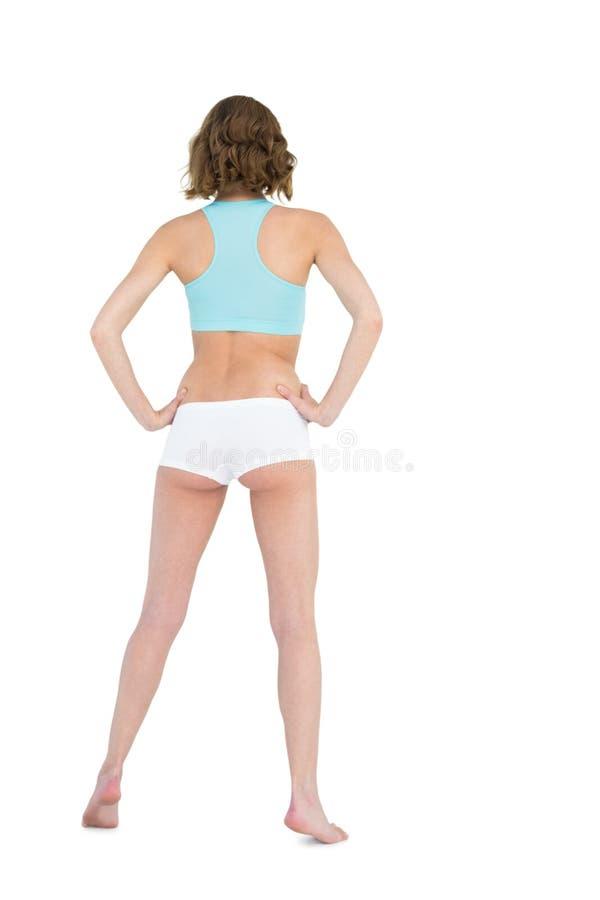 Retrovisione degli abiti sportivi d'uso della giovane donna snella che posano con le mani sulle anche fotografia stock
